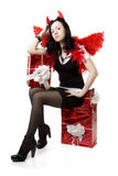 Girl in a devil costume with a gift. Picture of a girl in a devil costume with a gift royalty free stock photography