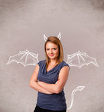 Girl with devil horns and wings drawing Royalty Free Stock Photography