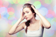 Girl in a diadem. Beautiful girl is putting on a diamond diadem and admiring herself, colorful pastel background Stock Images