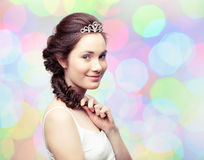 Girl in a diadem. Beautiful young woman with a braid wearing a diamond diadem Royalty Free Stock Image