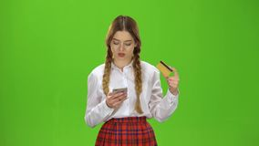 Girl dials numbers on the phone with a gold card. Green Screen stock video