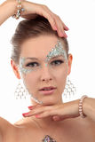 Girl with diamond make-up. Girl looking straight in the camera framing her head with both hands with diamond make-up, silver necklace and silver earring on a Stock Photo