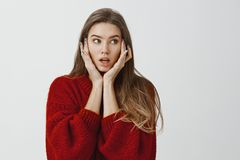 Girl did not know what to do after shocking revelation. Indoor shot of worried attractive caucasian woman in stylish red. Sweater, holding palms on face and Stock Image