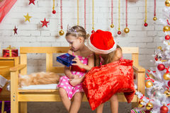 The girl did not like the gift that gives her another girl dressed as Santa Claus Stock Photography