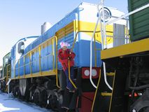 Girl on diesel locomotive. Young girl on  footboard of old russian diesel locomotive Royalty Free Stock Photography
