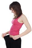 Girl after of a diet. Attractive girl after becoming thin by a diet a over white background Royalty Free Stock Photos