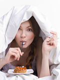 Girl on diet eating spoon. Instead of dessert  under white cover on white background Stock Image