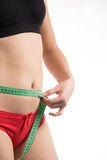Girl on a diet measuring waist and abdomen centimeter and looks Royalty Free Stock Photography