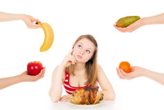 The girl on a diet thinks to choose Stock Photos