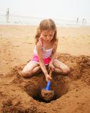 A Girl Digging at the Beach Stock Photos