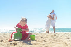 Girl digging sand on beach with parents in background Stock Images