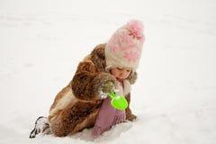 Girl digging snow Stock Photos