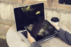 Girl with digital tablet, coffee to go and laptop on the wooden Royalty Free Stock Photos