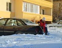 Girl digs car out of the snow Stock Images