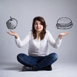Girl with a dilemma about food Stock Photography