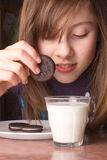 Girl Dipping Cookies. A cute girl dipping her cookies in milk royalty free stock photos