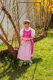 Girl in the dirndl is bored with coloured ones wobble in the hand Royalty Free Stock Image