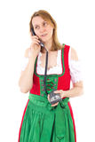Girl in dirndl calling her boyfriend to pick her up Stock Images