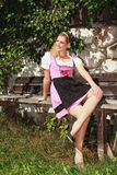 Girl in dirndl sunning himself on a bench Royalty Free Stock Photography