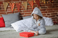 The girl is disappointed with the Christmas gift. Stock Image