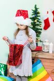 Girl with disappointed face looking into the bag with Christmas present Stock Photography