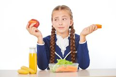 Girl disappointed by her healthy lunch at school Stock Photography