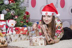 Girl disappointed a little gift, lying near the Christmas tree Royalty Free Stock Photos