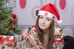 Girl disappointed a little gift, lying near the Christmas tree Stock Photo