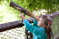Girl discovers through old-style telescope. Little inquisitive girl preschooler discovers surroundings on observation balcony in spring park through old-style Stock Images