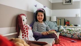 Girl disguised as a butterfly reading with her doll Stock Photo