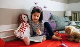 Girl disguised reading a book to her doll Royalty Free Stock Photo