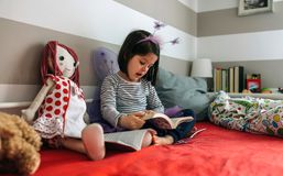 Girl disguised reading a book to her doll Stock Photos