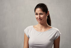Girl disgusted face expression. Young woman disgusted squeamishness over gray wall background Stock Image