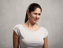 Girl disgusted face expression. Young woman disgusted squeamishness over gray wall background Stock Photography
