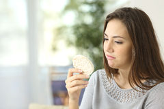 Girl disgusted looking a dietetic cookie Royalty Free Stock Images