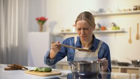 Girl disgusted with stinky meal on stove, spoiled ingredients, untasty food