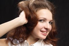 Girl dishevelled hair by hand isolated black Stock Images