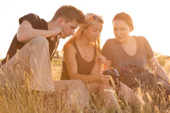 Girl displaying images on her camera to brother. Family of three people sitting on grassy lawn watching on display of photo camera back light sun sunset sun on Royalty Free Stock Images