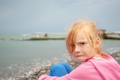 The girl with a displeased facial expression on the beach. The redhead girl with a displeased facial expression on the beach stock image