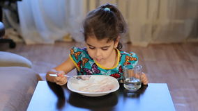 Girl distracted while eating. Little girl eats porridge. Looking away stock footage