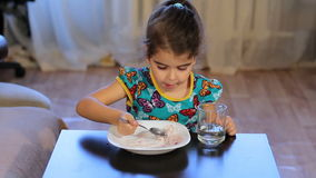 Girl distracted while eating. Little girl eats porridge. Looking away stock video