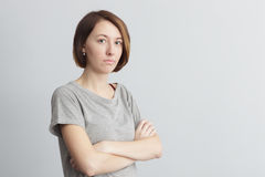 Girl with distrust and doubt looks forward, her arms crossed ove. Offended and dissatisfied girl crossed her arms at chest Stock Image