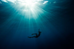 Girl dive underwater. Deep blue sea with sun rays stock image