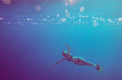 Girl dive underwater. Soft focus and vintage style royalty free stock photos
