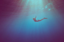 Girl dive underwater. Vintage color style stock photos