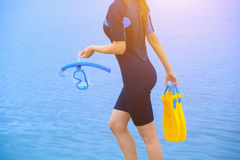 Girl Diver In A Wet Suit Holds A Mask With A Blue Tube In Her Hands And A Yellow Fin In The Other Hand. Royalty Free Stock Photos