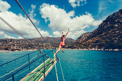 Girl dives or jumps. With a long jump from the boat into the open sea in a landscape with mountains. Vintage toned image. Stylish toned picture Royalty Free Stock Photography