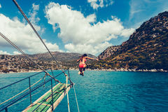 Girl dives or jumps. With a long jump from the boat into the open sea in a landscape with mountains. Vintage toned image. Stylish toned picture Royalty Free Stock Photos