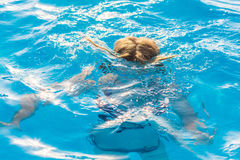 Girl dives in the pool with glasses for swimming. The girl dives in the pool with glasses for swimming Stock Images