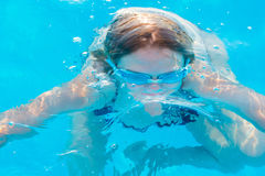 Girl dives in the pool with glasses for swimming. The girl dives in the pool with glasses for swimming Royalty Free Stock Photography